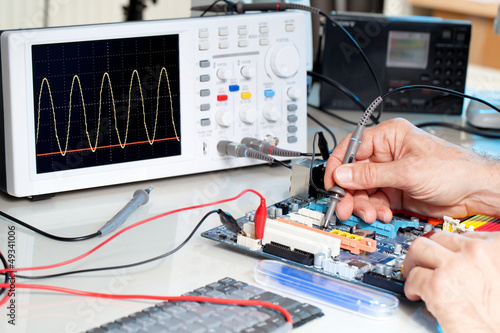 Fotografie, Obraz  Tech tests electronic equipment in service centre.
