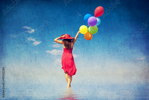 Photo  Brunette girl with colour balloons at coast.