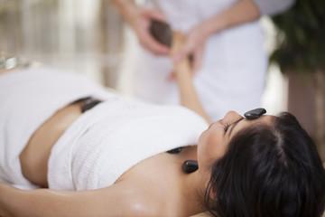 Obraz na płótnie Canvas Pretty young woman getting a stone massage at a spa