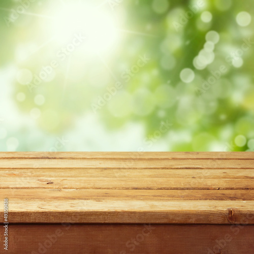 Fotografía  Empty wooden deck table with foliage bokeh background
