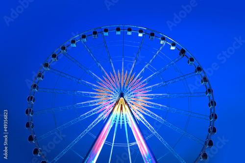 Deurstickers Antwerpen Bright multicolored spinning ferris Wheel in blue sky.