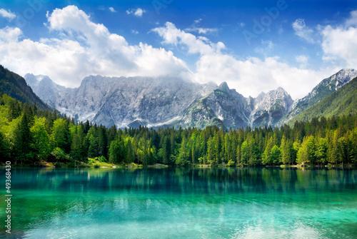 Türkisfarbener See mit Wald und Bergen