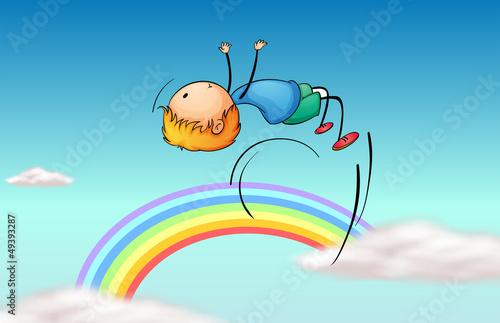 In de dag Regenboog A boy jumping in the sky and a rainbow