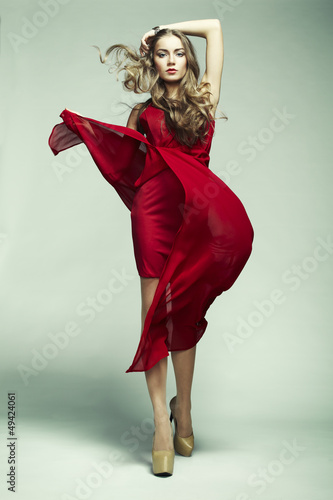 Plakát Fashion photo of young magnificent woman in red dress