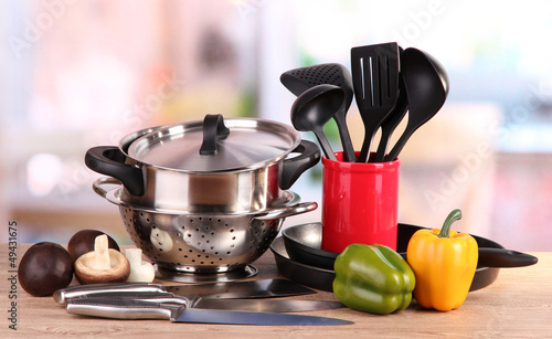 Fotografía  composition of kitchen tools and vegetables on table in kitchen