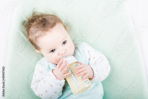 9670efc4c Cute baby in a green sweater drinking milk from a bottle - Buy this ...