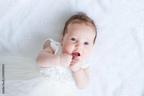 Fotografia Blue eyed baby girl in a white dress