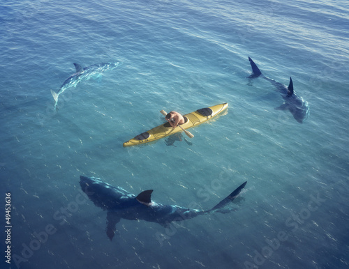 czlowiek-na-lodce-na-srodku-oceanu-otoczony-przez-rekiny