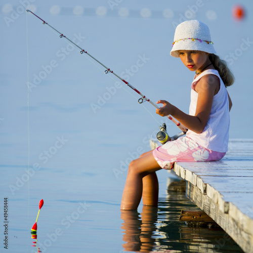 Foto op Canvas Vissen Fishing - girl fishing on the pier