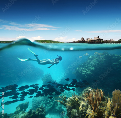Foto op Canvas Onder water Young woman snorkeling in the coral reef in the tropical sea