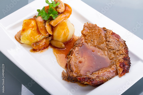 Roast pork with gravy and potatoes on the plate Poster