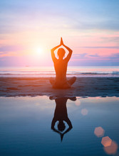 Silhouette Of A Woman Yoga On Sea Sunset With Reflection.