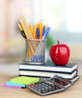 School supplies with red apple on wooden table