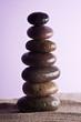 six wet stones in the sand,blackground purple
