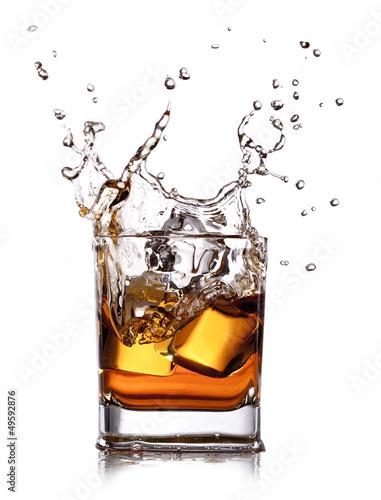 Fotografia whiskey splash with ice cubes isolated on white