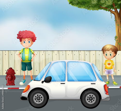 A boy and a child at the street with a car