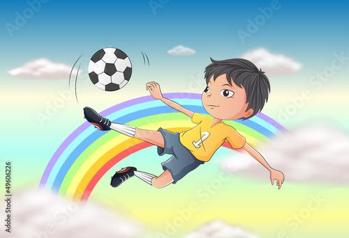 In de dag Regenboog A boy playing soccer