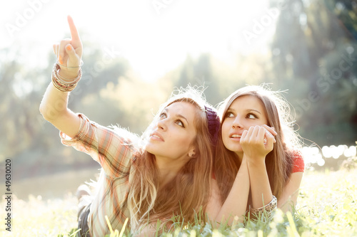 Fotografie, Obraz  two girlfriends outdoor looking upwards