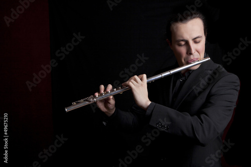 Stampa su Tela professional flutist musician playing flute on black background