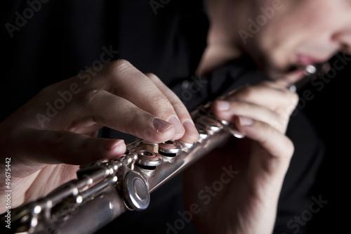 professional flutist musician playing flute on black background Fototapeta