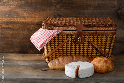 Deurstickers Picknick picnic basket with bread and cheese on wood