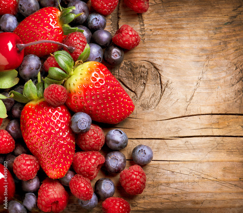Berries on Wooden Background. Organic Berry over Wood Wall mural