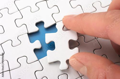 Fotografie, Obraz  A person fitting the last puzzle piece.
