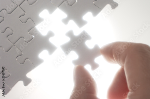 Fototapety, obrazy: A person fitting puzzle pieces against the light.