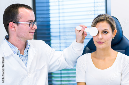 Fotografía  Optometry concept - pretty young woman having her eyes examined