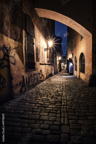 Photo Stands Narrow alley narrow alley with lanterns in Prague at night