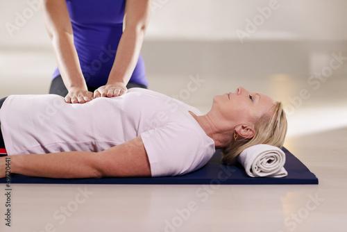 Fotografia  Young therapist doing reiki therapy to senior woman