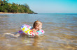 little girl in the sea with rubber ring