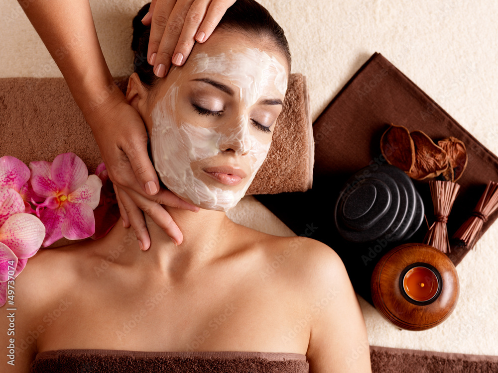 Fototapeta Spa massage for woman with facial mask on face