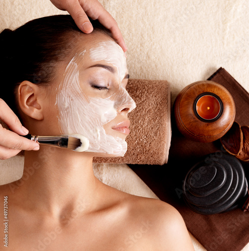 Spa therapy for woman receiving facial mask Canvas Print