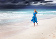 The woman in a long blue dress in a surf of stormy sea..