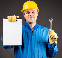 Portrait Of A Young Worker Holding A Blank Clipboard And A Wrenc