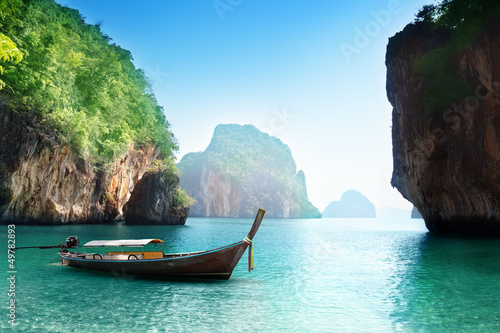 Photo Stands Black boat on beach of island in Krabi Province, Thailand