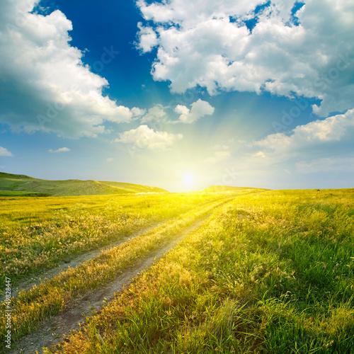 Foto auf Gartenposter Hugel Summer landscape with green grass, road and clouds
