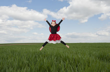 Little Girl In Lady Bug Costume Jumping In The Fileds