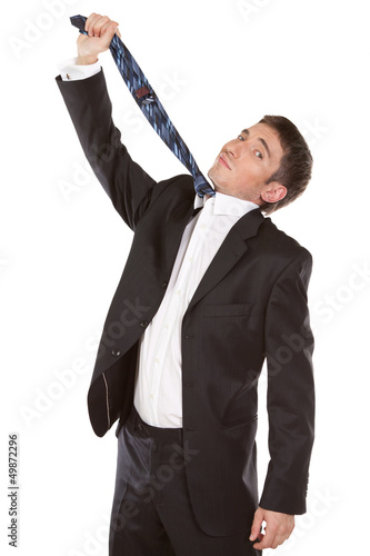 Fotografie, Obraz  mid-adult man pulling necktie out to choke himself while making