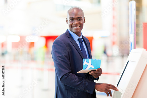 Fototapety, obrazy: african businessman using self service check in machine