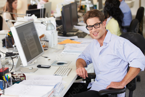 Fototapety, obrazy: Man Working At Desk In Busy Creative Office