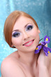 Beautiful young woman with glamour make up and flower
