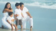 Attractive Hispanic family sitting together on beach
