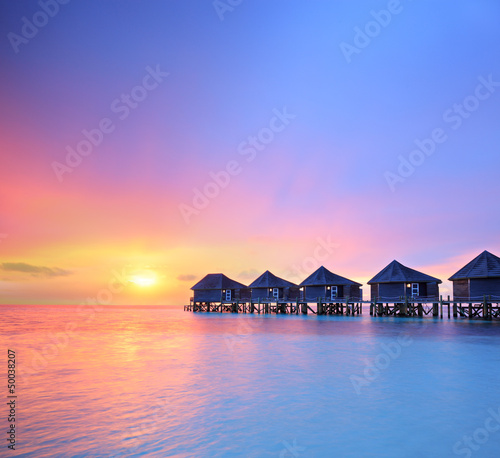 View of a beautiful sunset on a Malidves island and water villas