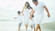 Hispanic family spending summer vacation on beach holding hands