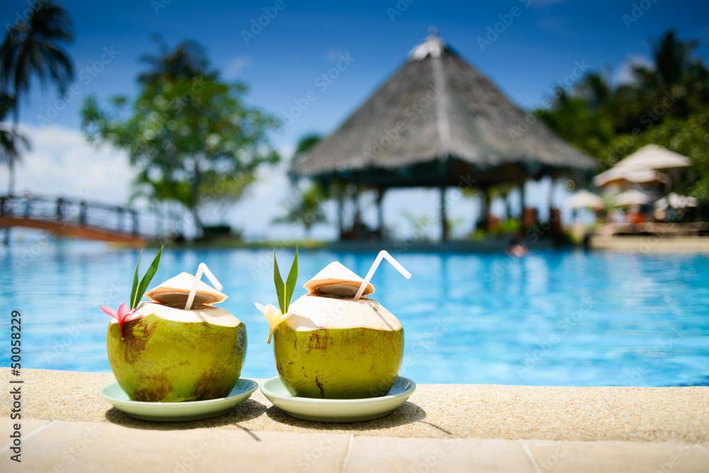 Fototapeta Pina colada drink in front of pool