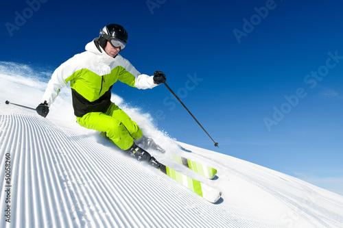 Fotobehang Wintersporten Skier in mountains, prepared piste and sunny day