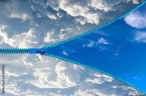 Foto  Öffnen eines Reißverschlusses auf einem blauen Himmel