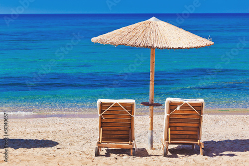 view of the beach with chairs and umbrellas Poster